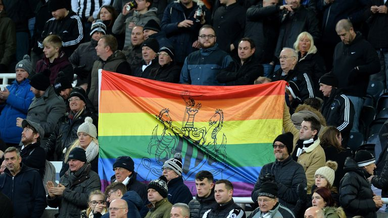 Newcastle fans hold up a rainbow flag at St James' Park