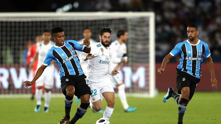 Bruno Cortez of Gremio is challenged by Real Madrid midfielder Isco