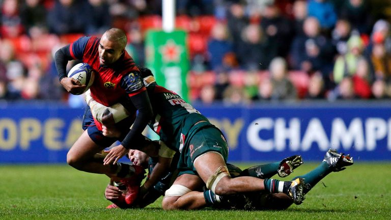 Simon Zebo of Munster is tackled by Mike Williams and Tino Mapapalangi of Leicester Tigers