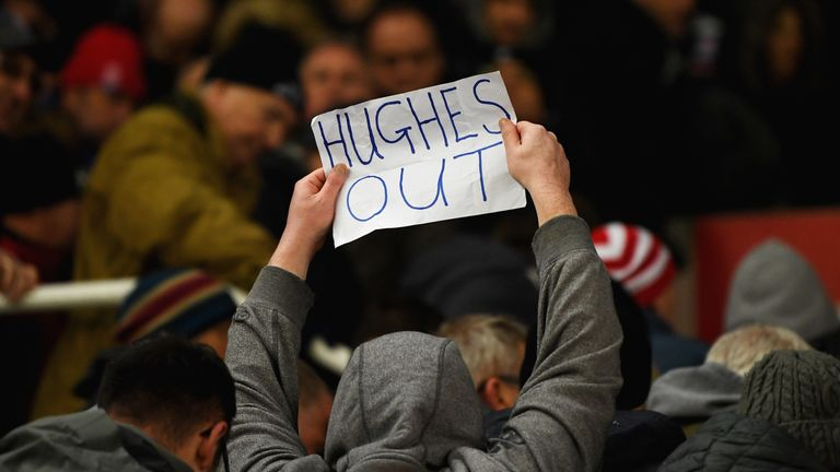 A fan holds a 'Hughes out' sign during Stoke's defeat to Newcastle