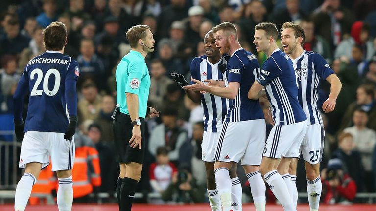 West Brom players protest with Craig Pawson at one VAR decision