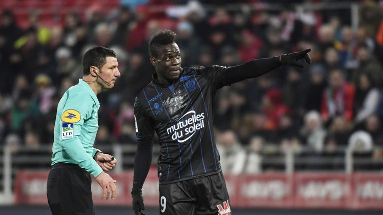 Balotelli (R) talks with French referee Nicolas Rainville (L) during the match against Dijon