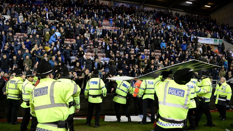 An advertising board was thrown at police as they attempted to prevent a pitch invasion