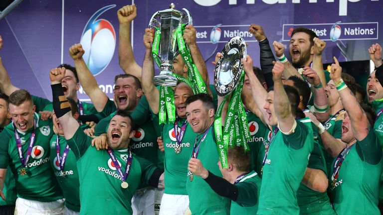 Ireland's Peter O'Mahony (C) and teammates celebrate with the trophy after winning the Grand Slam