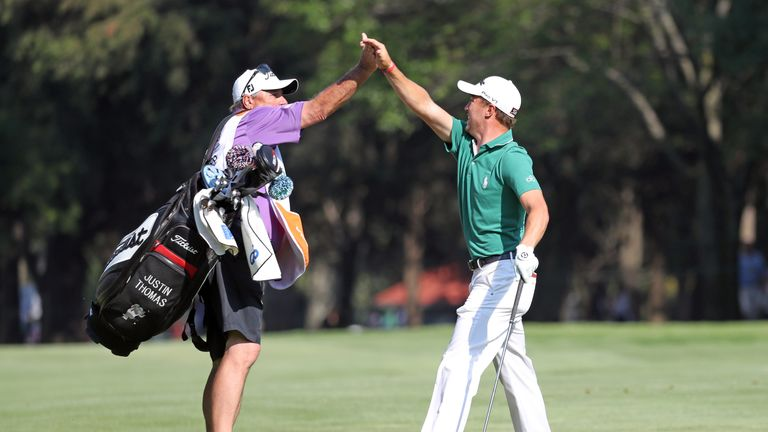 Justin Thomas celebrates with his caddie after his eagle at the 18th