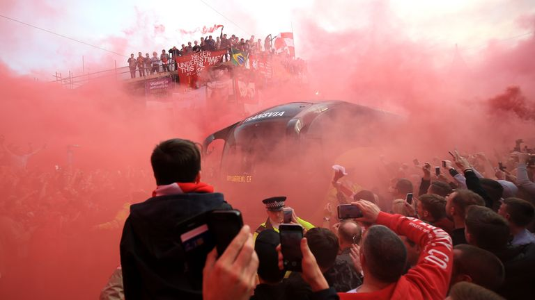 Liverpool fans light flares and surround the Villarreal team bus prior to the game