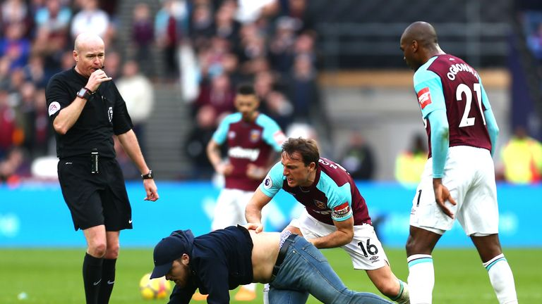 Mark Noble clashed with one of several pitch invaders during the defeat to Burnley