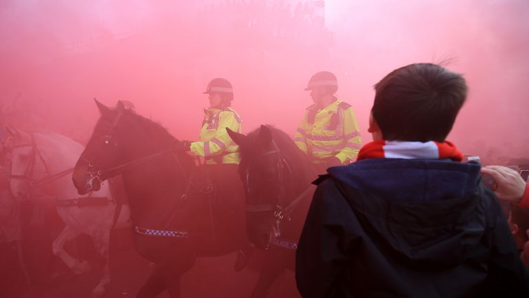 Mounted Police surrounded by Liverpool fans and in red smoke
