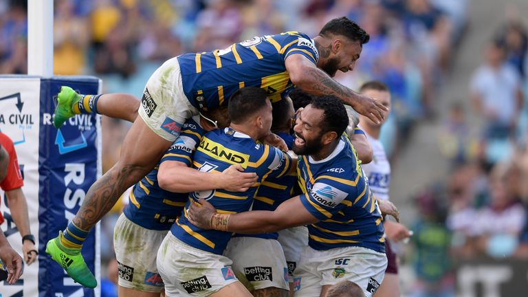 Clinton Gutherson of the Eels celebrates scoring a try with team mates