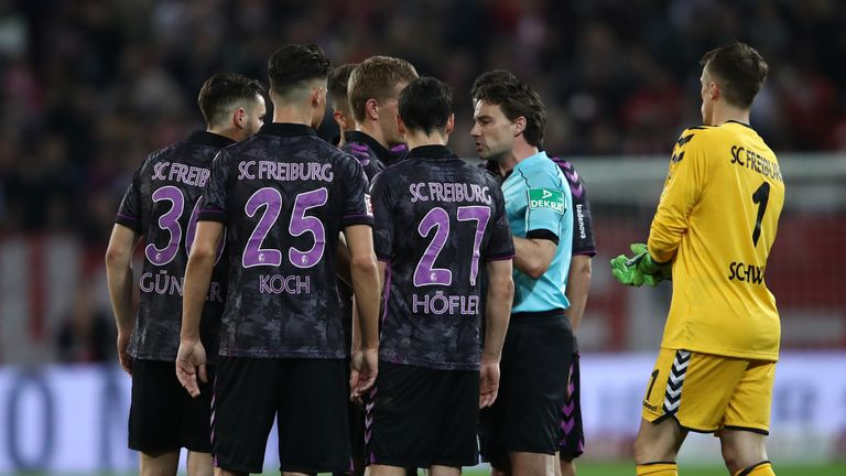 Freiburg player surround referee Guido Winkmann