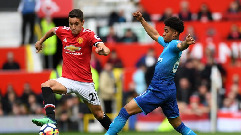Ander Herrera (L) vies with Reiss Nelson (R)