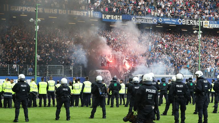Riot police ran on to the pitch at the Volksparkstadion after fans began throwing flares