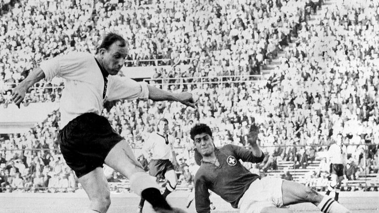 Swiss defender Heinz Schneiter attempts to block the shot of German forward Uwe Seeler