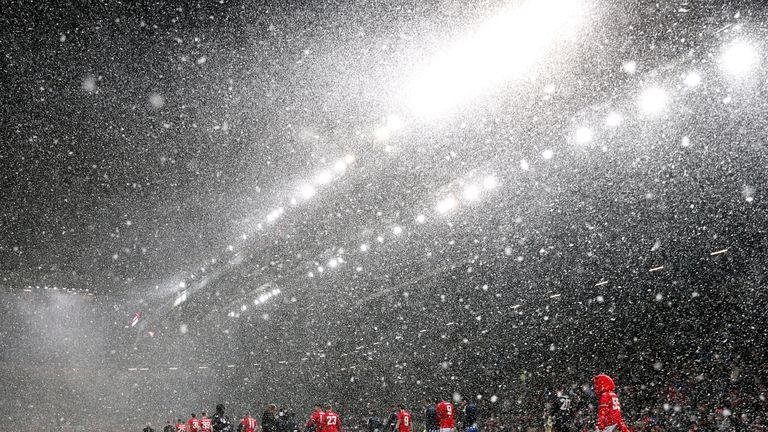 Manchester United and Brighton players walk out into heavy snow before the Emirates FA Cup, quarter-final match at Old Trafford