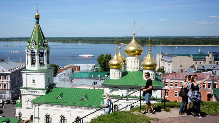Tourists take pictures in front of the Volga river embankment in central Nizhny Novgorod