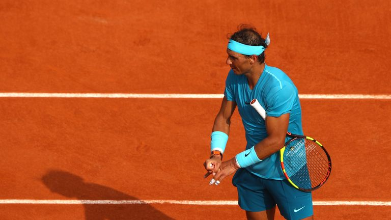 Nadal stretches his fingers after suffering from cramp