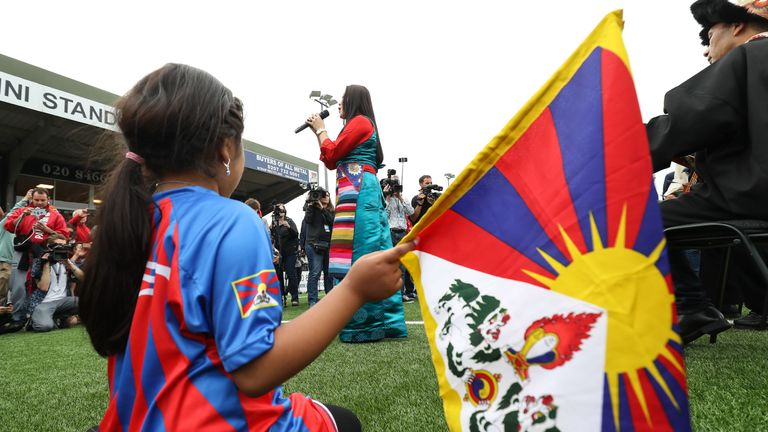 A young Tibet fan watches the opening ceremony