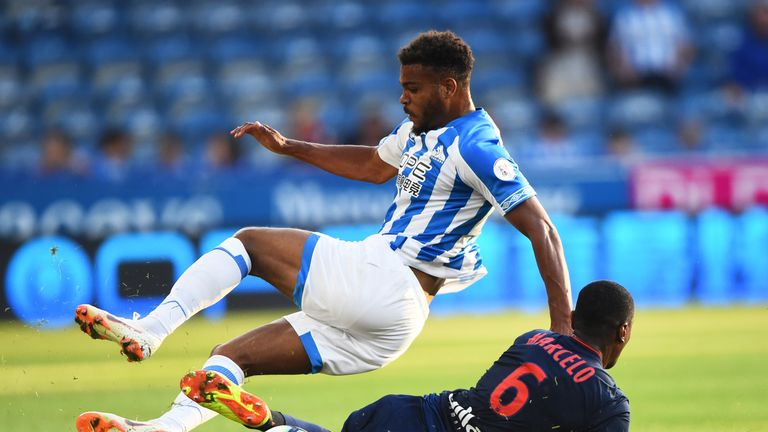 Steve Mounie of Huddersfield jumps a tackle against Lyon