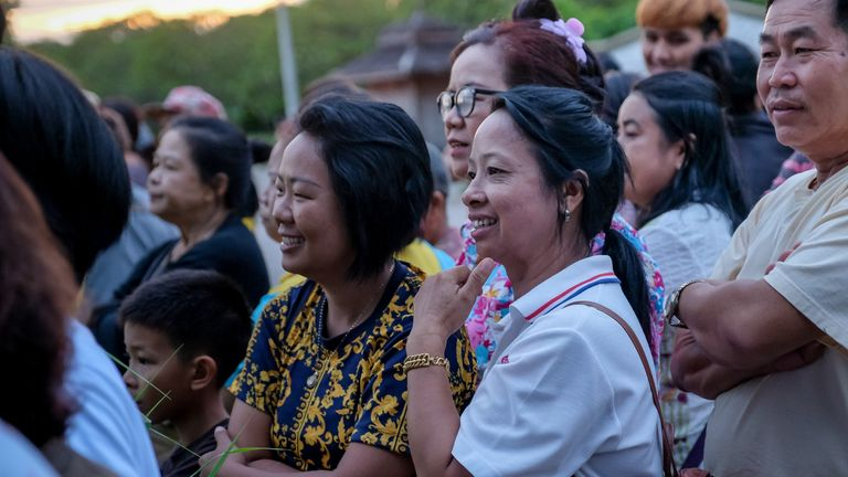 Onlookers watch and cheer as ambulances transport rescued boys in Thailand