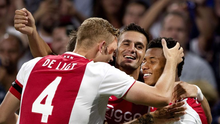 Ajax's Brazilian forward David Neres (R) celebrates with teammates after scoring their 3-0 goal against Standard Liege