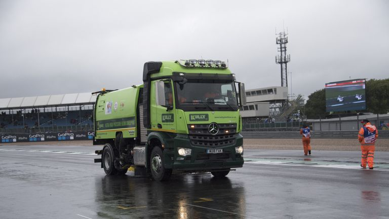 Marshall staff attempt to clean and dry the Silverstone track