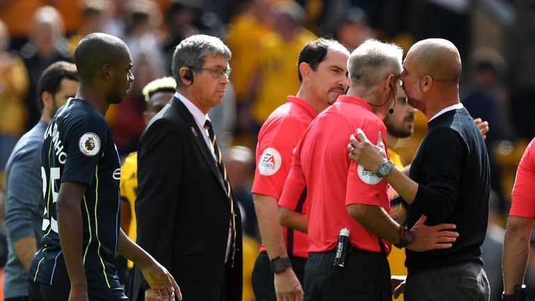 Pep Guardiola speaks with the officials on the pitch after Man City's draw at Wolves