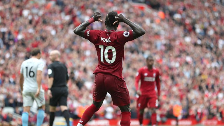 Sadio Mane gestures toward his name on the back of his after scoring Liverpool's second goal