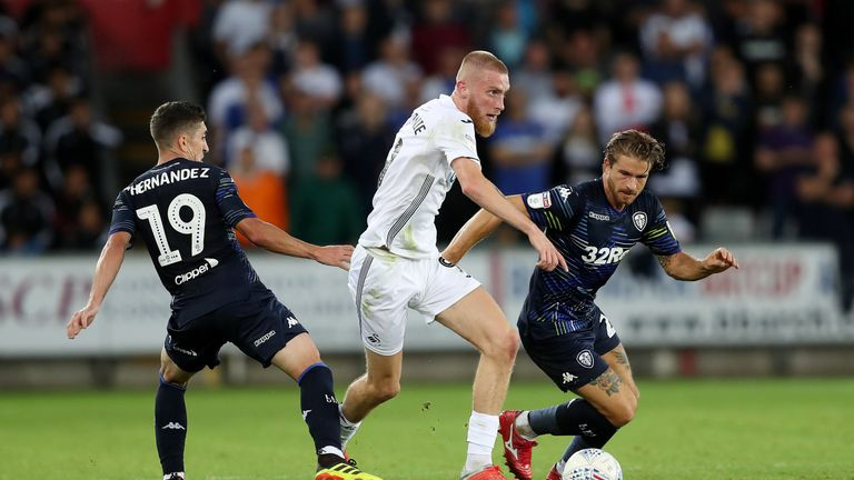 "Swansea City's Oli McBurnie gets away from Leeds Pablo Hernandez and Gaetano Berardi during the Sky Bet Championship match at the Liberty Stadium, Swansea. PRESS ASSOCIATION Photo. Picture date: Tuesday August 21, 2018. See PA story SOCCER Swansea. Photo credit should read: David Davies/PA Wire. RESTRICTIONS: EDITORIAL USE ONLY No use with unauthorised audio, video, data, fixture lists, club/league logos or ""live"" services. Online in-match use limited to 120 images, no video emulation. No use in betting, games or single club/league/player publications."