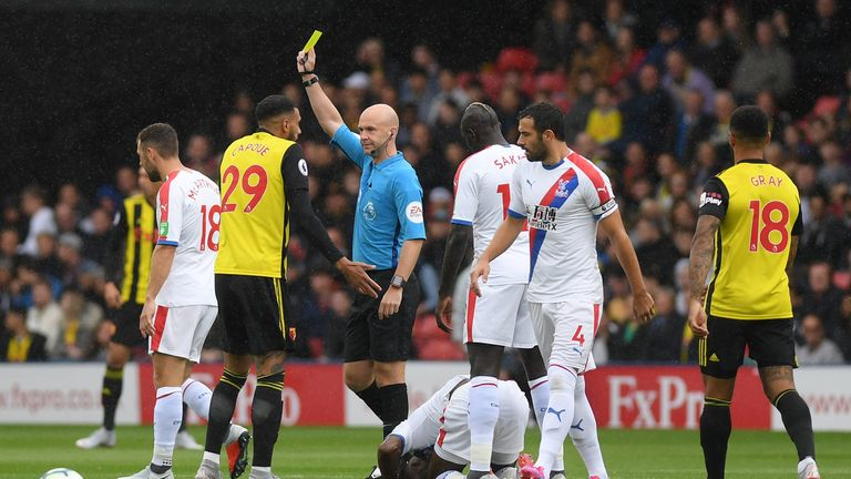 Watford midfielder Etienne Capoue (left) is booked by Anthony Taylor