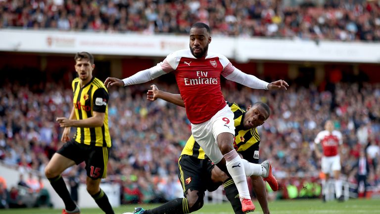 Alexandre Lacazette is challenged in the Watford penalty area