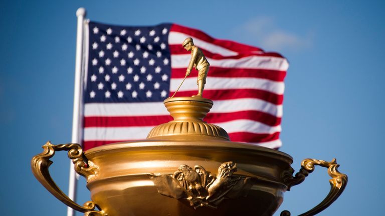 The American flag flies behind a statue of the Ryder Cup trophy at Hazeltine National Golf Course in Chaska, Minnesota, September 26, 2016