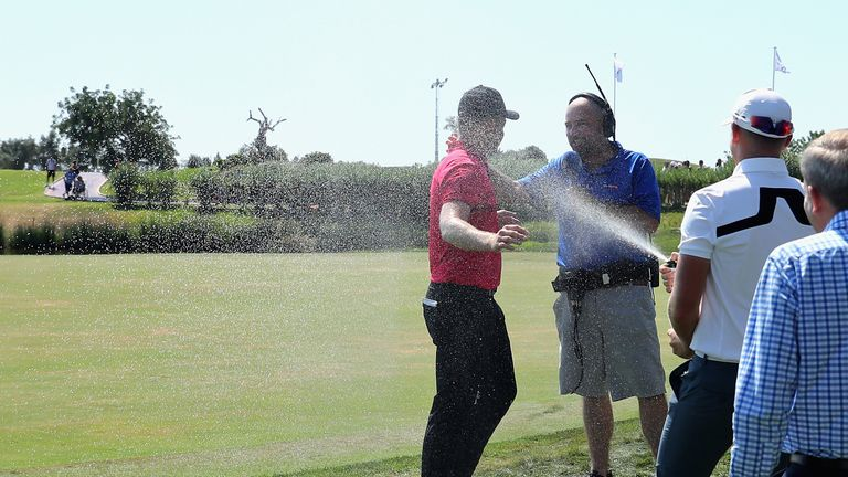 Fisher is sprayed with champagne by Matt Wallace as he speaks to Sky Sports Golf