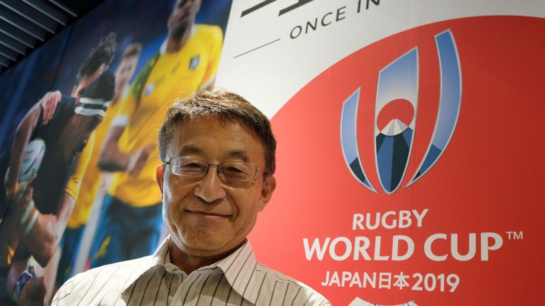 Koji Tokumasu, senior director of the World Cup organising committee and former Asia Rugby boss, posing with the logo of the 2019 Rugby World Cup, in Tokyo