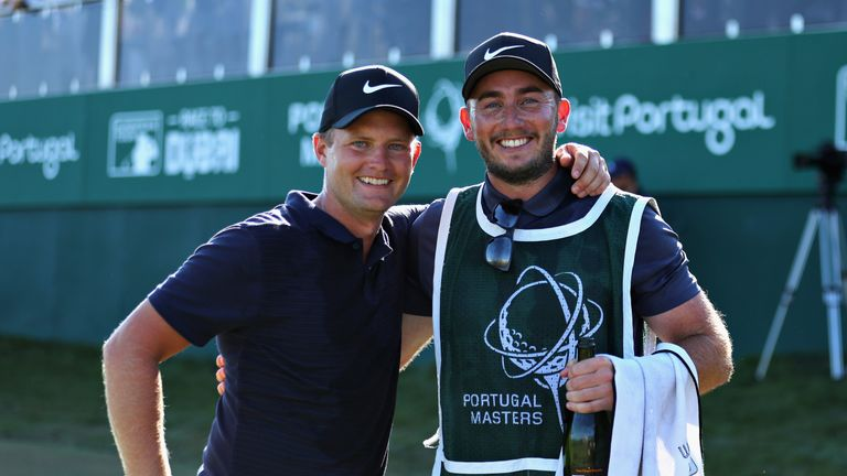 Lewis celebrates with his caddie Jonathan Bell on the 18th green
