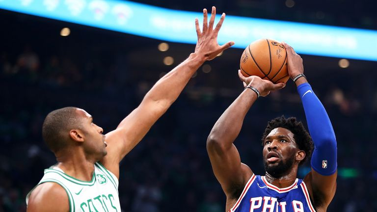 Joel Embiid shoots while guarded by Al Horford