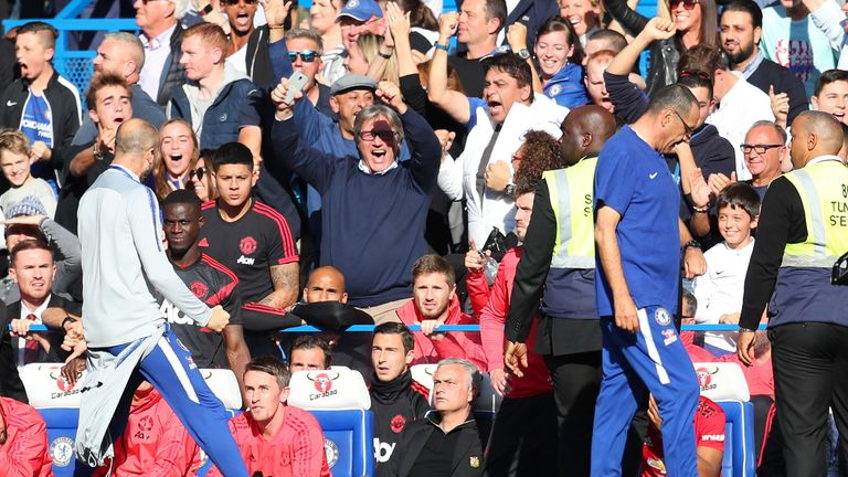 A member of Chelsea's backroom staff celebrates their stoppage time equaliser in front of Jose Mourinho