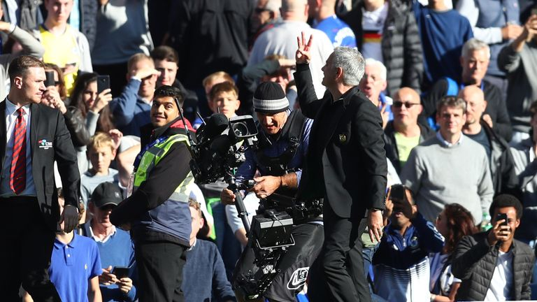 Jose Mourinho holds up three fingers as he gestures towards fans