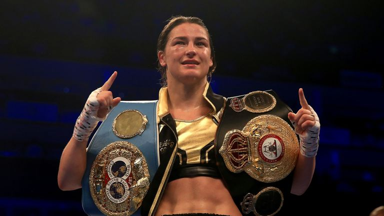Taylor hoists the WBA and IBF belts after her most recent win against Kimberly Connor