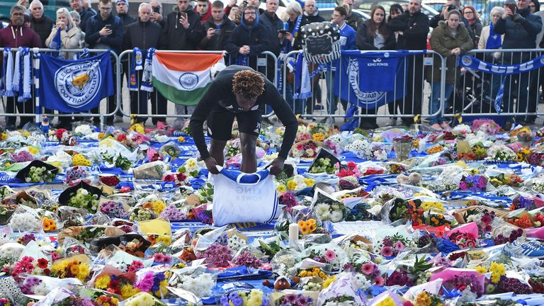 Leicester City youth team player Darnell Johnson lays a football shirt among floral tributes left to the victims of the helicopter crash which killed chairman Vichai Srivaddhanaprabha.