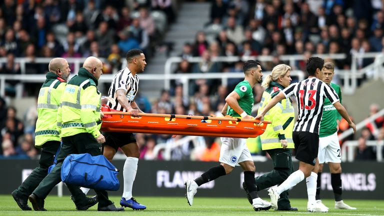 Players help paramedics carry a stretcher following a clash of head between Glenn Murray and Federico Fernandez