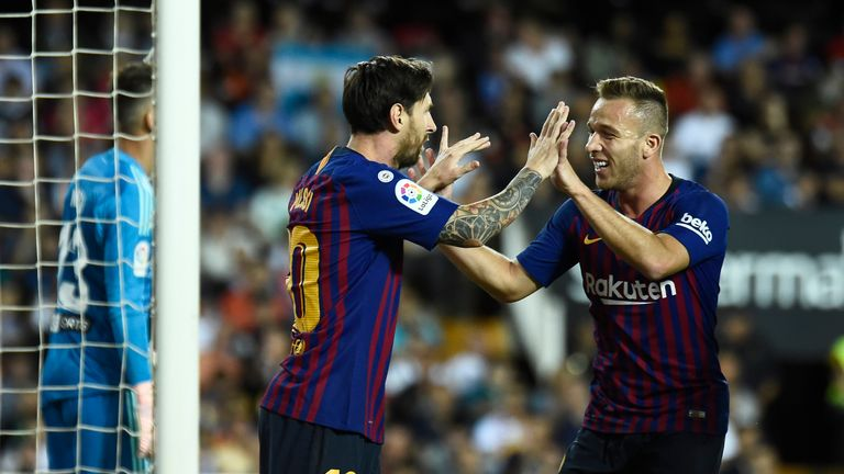 Arthur celebrates a Barcelona goal with Lionel Messi