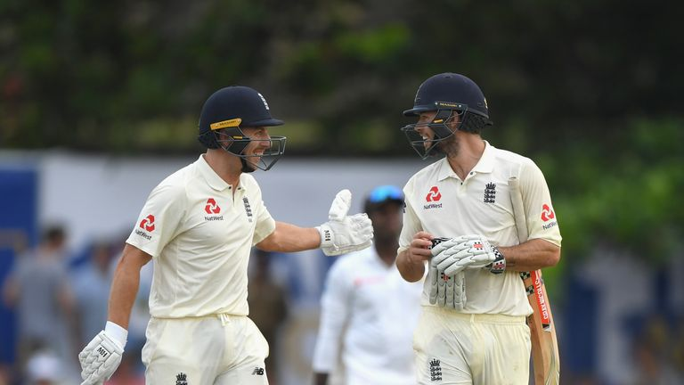 Foakes (right) is congratulated by not-out partner Jack Leach as the pair leave the field with England 321-8