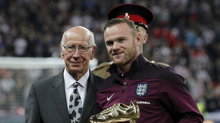 Sir Bobby Charlton hands Rooney his golden boot having broken his goalscoring record