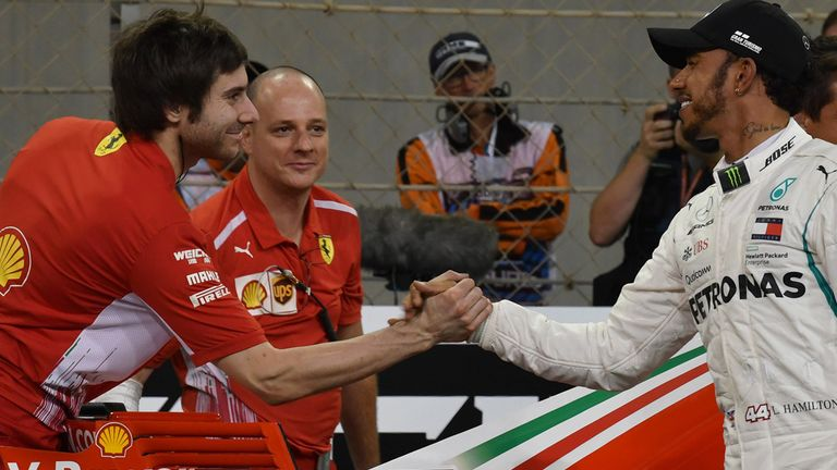 Friendly rivals: Hamilton shook hands with all the Ferrari team members around Vettel's car after qualifying