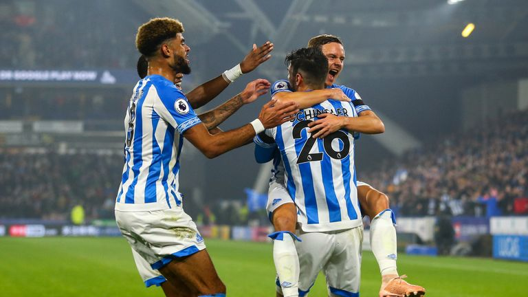 Huddersfield players celebrate after Timothy Fosu-Mensah's own-goal