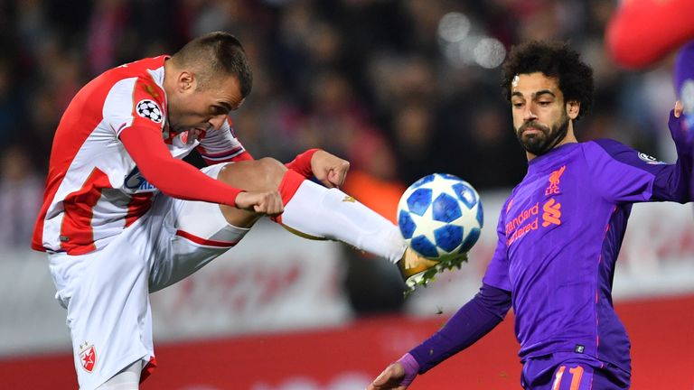 Red Star Belgrade midfielder Nenad Krsticic (L) vies for the ball with Liverpool forward Mohamed Salah