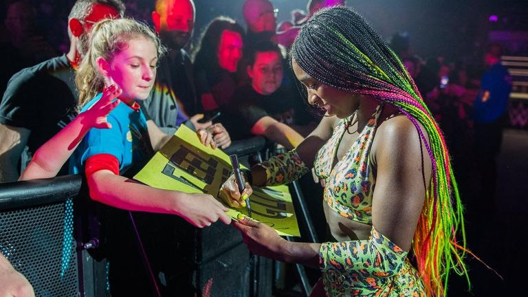 Naomi signs a young fan's poster in support of her at the WWE event in Nottingham