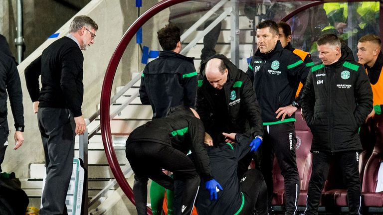 Hibernian manager Neil Lennon is helped to his feet after appearing to be struck by an object from the crowd
