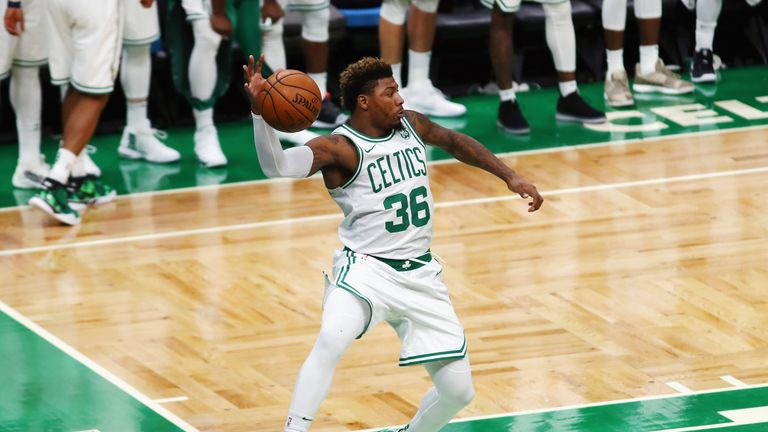 Marcus Smart leaps to keep a ball in play