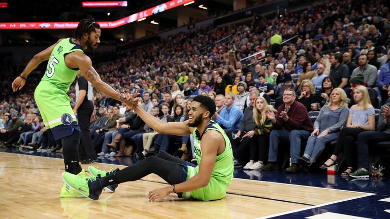 Derrick Rose #25 of the Minnesota Timberwolves helps teammate Karl-Anthony Towns #32 of the Minnesota Timberwolves from the floor during the game against the Denver Nuggets on November 24, 2018 at Target Center in Minneapolis, Minnesota.